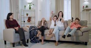 Una madre atractiva sonriente con sus tres ni?os y una abuelita que pasa un rato agradable junto mientras que hermana grande con  almacen de metraje de vídeo
