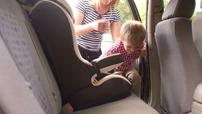 Una madre ayuda a su hijo a subir en un coche y a sentarse en un asiento del niño del automóvil almacen de video
