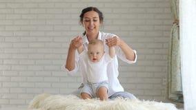 Una madre blanda joven celebra a su bebé recién nacido al lado de las manos, el bebé salta metrajes