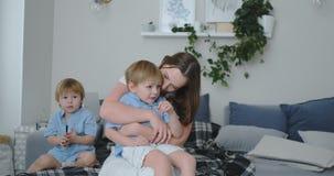 Una madre cariñosa en un vestido que se sienta en diwanie abraza su hijo y besos Armonía y comprensión felices de la familia metrajes