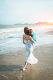 Una madre celebra a su pequeña hija en sus brazos en la playa y va al mar Imagenes de archivo