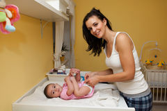 Una madre che cambia il suo pannolino della figlia del bambino. Immagine Stock Libera da Diritti