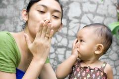 Una madre che insegna alla sua neonata arrivederci ad un bacio Fotografia Stock