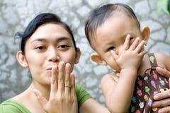 Una madre che insegna alla sua neonata arrivederci ad un bacio Immagine Stock