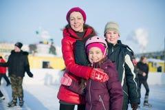 Una madre con due bambini che stanno sulla pista di pattinaggio all'aperto Immagini Stock Libere da Diritti