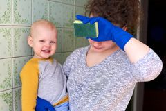 Una madre con su peque?o hijo est? limpiando la casa El concepto de combinar la preparaci?n y de criar a un ni?o fotografía de archivo