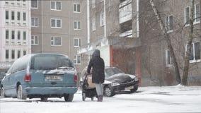 Una madre con un bambino in un passeggiatore cammina in precipitazioni nevose pesanti archivi video