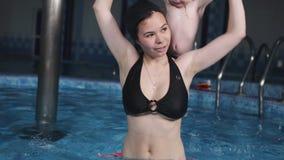 Una madre con un piccolo figlio nel centro di forma fisica dello stagno sta facendo la ginnastica dell'acqua stock footage