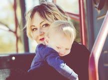 Una madre conforta il suo bambino gridante su un campo da giuoco fotografia stock libera da diritti