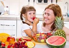 Una madre da a la niña una ensalada de fruta en la cocina Fotos de archivo libres de regalías