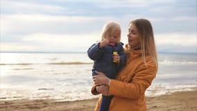 Una madre del adulto celebra a una hija joven que sople burbujas de jabón cerca de la playa metrajes