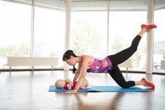 Una madre di sport sopra un bambino fa un'oscillazione con il suo piede Fotografia Stock Libera da Diritti