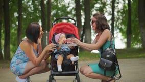 Una madre e la sua amica che occupano elasticità il bambino in un passeggiatore stock footage