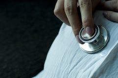 Una madre está escuchando su vientre usando un estetoscopio Imagen de archivo libre de regalías