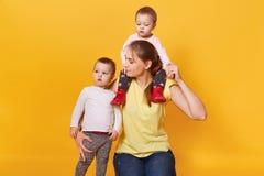 Una madre feliz celebra un niño en su cuello y otro abrazo firmemente, teniendo fines de semana divertidos junto, ocupándose a su imagen de archivo