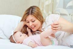 Una madre feliz con un bebé juega en una cama fotos de archivo