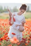 Una madre feliz con un pequeño hijo en sus brazos en el campo sin fin de amapolas rojas en un día de verano soleado imagen de archivo
