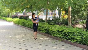 Una madre feliz joven camina con un bebé recién nacido en el tiempo caliente en el parque almacen de metraje de vídeo