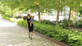 Una madre feliz joven camina con un bebé recién nacido en el tiempo caliente en el parque metrajes