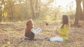 Una madre feliz y una pequeña hija linda que se sientan junto y que juegan con la manzana en un parque de la ciudad en una comida almacen de metraje de vídeo