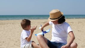 Una madre feliz y su hijo se están sentando en una playa arenosa en un día de verano soleado y están jugando con un avión del jug metrajes