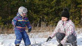 Una madre feliz y su niño que juegan bolas de nieve en el bosque, en la cámara lenta El concepto de una familia feliz almacen de video