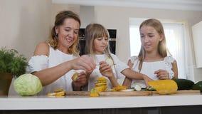 Una madre hermosa con dos niños en la ropa blanca hace una pirámide de calabacín amarillo tajado en la tabla de cocina adentro almacen de metraje de vídeo