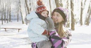Una madre hermosa con su hijo disfruta del tiempo soleado frío en el parque en el invierno metrajes