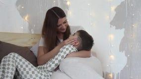 Una madre hermosa está jugando con su hijo que se sienta en la cama que tiene un buen humor metrajes