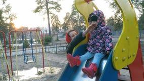 Una madre hermosa joven toma cuidado de su hija en una chaqueta colorida que se siente en una diapositiva en un parque de la prim metrajes
