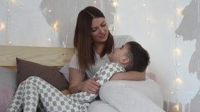 Una madre hermosa juega con su hijo que se sienta en la cama y lo besa que tiene un buen humor almacen de video
