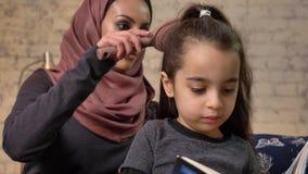 Una madre india joven que lleva un hijab que peina el pelo a su pequeña hija mientras que niño que lee un libro, sentándose en el almacen de video