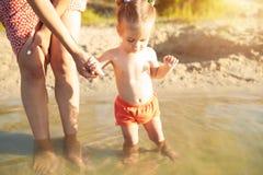 Una madre irreconocible joven que celebra a un pequeño bebé que aprende nadar Concepto de vacaciones de familia del verano fotografía de archivo libre de regalías