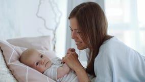 Una madre joven besa al bebé en la mejilla metrajes
