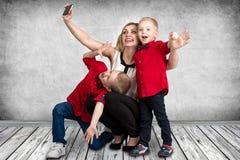 Una madre joven con dos hijos que hacen el selfie en el teléfono móvil Primavera, concepto de vacaciones de familia Imagen de archivo libre de regalías