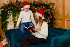 Una madre joven con su hijo que lee un libro para la Navidad imagenes de archivo