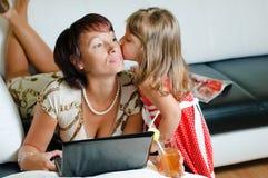 Una madre joven con un cuaderno y una hija Fotografía de archivo libre de regalías