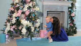 Una madre joven con un hijo recién nacido adornar el árbol de navidad en casa metrajes