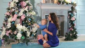 Una madre joven con un hijo recién nacido adornar el árbol de navidad en casa almacen de video