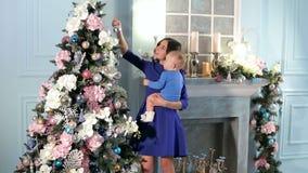 Una madre joven con un hijo recién nacido adornar el árbol de navidad en casa almacen de metraje de vídeo