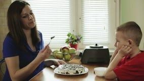 Una madre joven embarazada y un pequeño hijo han cocinado la torta y van a intentarla almacen de video