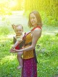Una madre joven en el vestido del este, deteniendo a un pequeño niño en un bebé foto de archivo libre de regalías