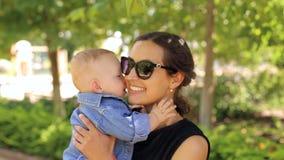 Una madre joven en gafas de sol camina en Sunny Park con su hijo recién nacido metrajes
