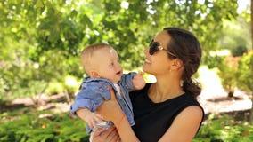Una madre joven en gafas de sol camina en Sunny Park con su hijo recién nacido almacen de video