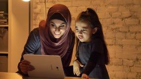 Una madre joven en un hijab se sienta con su pequeña hija en el sofá por la tarde y utiliza una tableta, mira un divertido metrajes