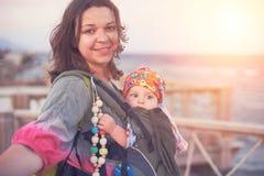 Una madre joven está en la playa con su bebé en una honda foto de archivo libre de regalías