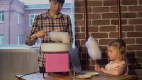Una madre joven hace el caramelo de algodón en una máquina especial para una pequeña hija almacen de video