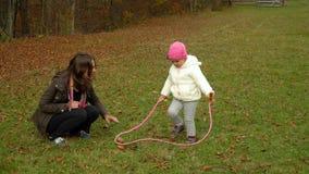 Una madre joven juega con su pequeña hija en el bosque del otoño que la pequeña muchacha hermosa aprende a la comba almacen de video