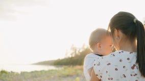 Una madre joven lleva a un pequeño hijo en sus brazos Paseo en la muchacha de la puesta del sol y el pequeño hijo metrajes