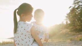 Una madre joven lleva a un pequeño hijo en sus brazos Paseo en la muchacha de la puesta del sol y el pequeño hijo almacen de metraje de vídeo
